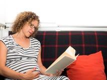 Beaux verres de port de femme enceinte se reposant sur le divan au sujet de Image stock