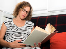 Beaux verres de port de femme enceinte se reposant sur le divan au sujet de Photographie stock