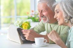 Beaux vieux couples lisant un journal Photos stock