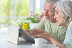 Beaux vieux couples lisant un journal Photographie stock