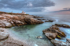 Beavertail Lighthouse at Sunset. This is a long exposure HDR photo of Beavertail Lighthouse at sunset near Jamestown in Rhode Island, USA. This is a rocky Stock Photo