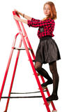 Beaytiful teen girl in checkered skirt. Standing on stepladder Stock Image