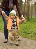Bebê que aprende andar no parque fotos de stock