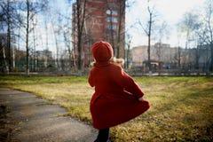 Bebé 3 años con el pelo largo En una boina y una capa rojas que hacen girar en la calle, en los rayos del sol El estado de Imagenes de archivo
