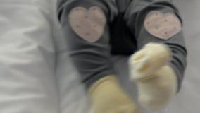 Bebé activo en calcetines y pantalones amarillos con los corazones metrajes