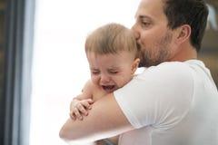 Bebé adorable con el padre sonsoling cerca de la ventana Imagen de archivo