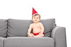 Bebé adorable con el sombrero de santa asentado en un sofá Foto de archivo