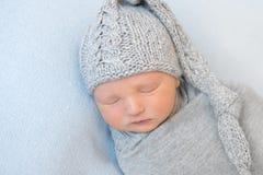 Bebé adorable con el sombrero gris hecho punto, tomando una siesta Imagen de archivo