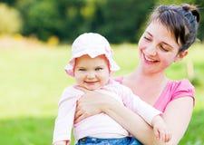 Bebé adorable con su madre Imagenes de archivo