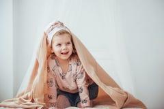 Bebé adorable, mirando hacia fuera debajo de una toalla foto de archivo