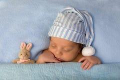 Bebé adorable que duerme en cama azul Foto de archivo libre de regalías