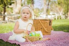 Bebé adorable que goza de sus huevos de Pascua en la manta de la comida campestre Imagen de archivo
