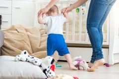 Bebé adorable que hace los primeros pasos con la madre en la sala de estar Imagenes de archivo