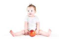 Bebé adorable que juega con una manzana roja grande Foto de archivo libre de regalías