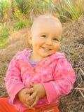 Bebé adorable que ríe en un prado - muchacha feliz Fotografía de archivo