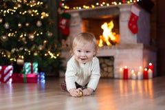 Bebé adorable que se arrastra en el piso en el cuarto adornado de la Navidad Fotografía de archivo libre de regalías