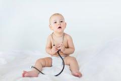 Bebé adorable que se sienta en la cama blanca con el estetoscopio Imágenes de archivo libres de regalías