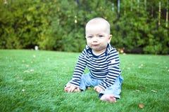Bebé adorable que se sienta en la hierba fotografía de archivo