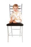 Bebé adorable que se sienta en una silla Fotos de archivo