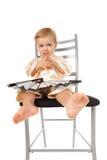Bebé adorable que se sienta en una silla y un pensamiento Fotos de archivo libres de regalías