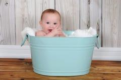 Bebé adorable que se sienta en washtub hapily verde imagen de archivo