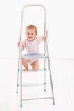Bebé adorable que sube en la sonrisa de la escalera Imagenes de archivo