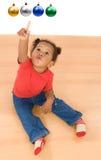 Bebé africano que señala cuatro bolas de la Navidad Imágenes de archivo libres de regalías