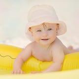Bebé alegre con el síndrome de los plumones que juega en la piscina Foto de archivo