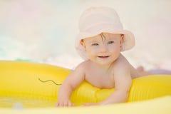 Bebé alegre con el síndrome de los plumones que juega en la piscina Foto de archivo libre de regalías