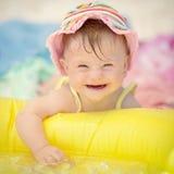 Bebé alegre con el síndrome de los plumones que juega en la piscina Imágenes de archivo libres de regalías