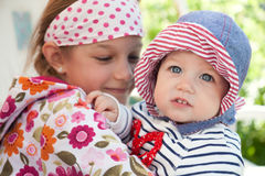 Bebé alegre divertido al aire libre con el abarcamiento de su hermana que simboliza unidad y felicidad Fotografía de archivo libre de regalías