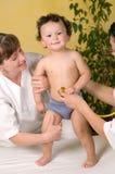 Bebé alegre en el doctor. Fotos de archivo
