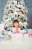 Bebé alegre positivo que se sienta con el regalo de la Navidad cerca del árbol de navidad Feliz Año Nuevo Fotografía de archivo