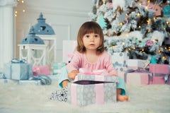 Bebé alegre positivo que se sienta con el regalo de la Navidad cerca del árbol de navidad Feliz Año Nuevo Imagen de archivo