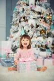 Bebé alegre positivo que se sienta con el regalo de la Navidad cerca del árbol de navidad Feliz Año Nuevo Imagenes de archivo
