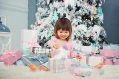 Bebé alegre positivo que se sienta con el regalo de la Navidad cerca del árbol de navidad Feliz Año Nuevo Fotos de archivo