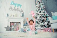 Bebé alegre positivo que se sienta con el regalo de la Navidad cerca del árbol de navidad Feliz Año Nuevo Imagen de archivo libre de regalías