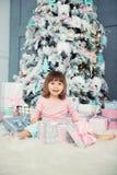 Bebé alegre positivo que se sienta con el regalo de la Navidad cerca del árbol de navidad Feliz Año Nuevo Imágenes de archivo libres de regalías