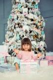 Bebé alegre positivo que se sienta con el regalo de la Navidad cerca del árbol de navidad Feliz Año Nuevo Fotos de archivo libres de regalías