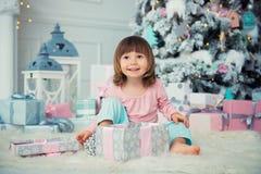 Bebé alegre positivo que se sienta con el regalo de la Navidad cerca del árbol de navidad Feliz Año Nuevo Foto de archivo