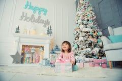 Bebé alegre positivo que se sienta con el regalo de la Navidad cerca del árbol de navidad Feliz Año Nuevo Foto de archivo libre de regalías