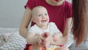 Bebé alegre que juega en palmas con la madre en casa almacen de video