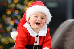 Bebé alegre vestido como Papá Noel en la Navidad imagenes de archivo