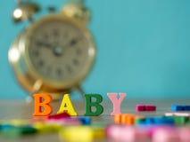 Bebé Alfabeto inglés hecho de color de madera de la letra El bebé del alfabeto en la tabla y despertador y fondo de madera del vi Foto de archivo