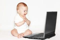 Bebé aplaudido con el cuaderno Imagen de archivo