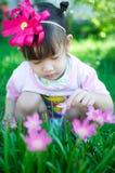 Bebé asiático con la flor Imagenes de archivo