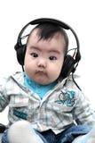 Bebé asiático con los auriculares Fotografía de archivo