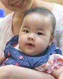 Bebé asiático con su mamá Fotos de archivo