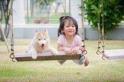 Bebé asiático del bebé en el oscilación con el perrito Foto de archivo