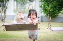 Bebé asiático del bebé en el oscilación con el perrito imagenes de archivo